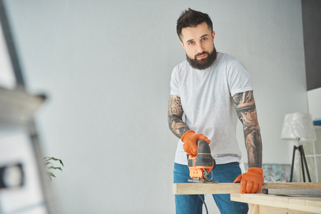 Handsome bearded tattooed man using electric jigsaw and looking at camera