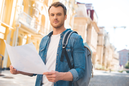 Handsome young tourist with backpack and map looking at camera on street