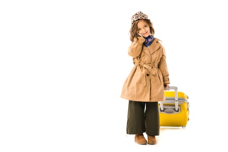 Adorable little child in trench coat with yellow suitcase talking by phone isolated on white background