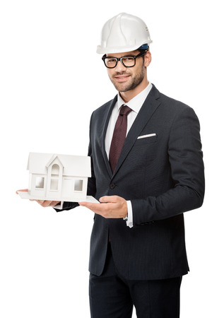 Young male architect in hard hat showing miniature house isolated on white background