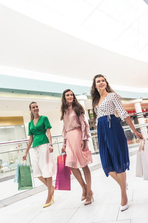 Smiling young women holding paper bags and looking away while walking together in shopping mall Stock Photo