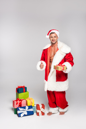 Sexy man in Santa costume holding Christmas present and showing thumb up on grey background
