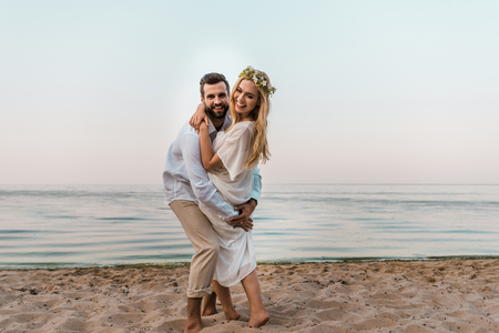 Laughing bride and groom hugging and looking at camera on beach