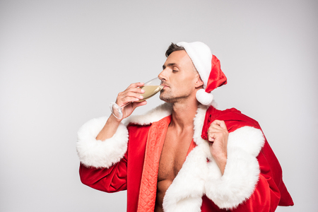 Handsome man in Santa costume drinking champagne isolated on grey background