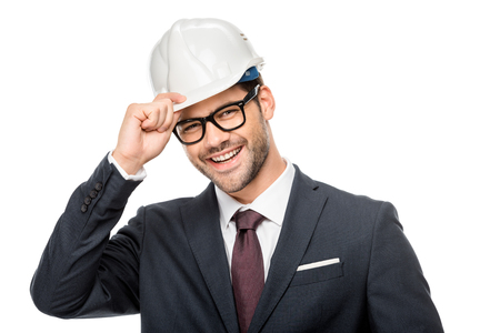 Portrait of laughing young male architect adjusting hard hat isolated on white background