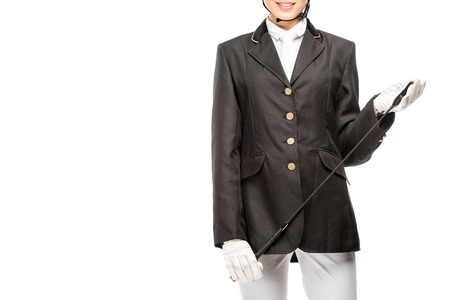 Cropped shot of smiling young horsewoman in uniform holding horseman stick isolated on white background Banco de Imagens
