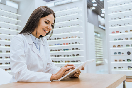 Smiling doctor using digital tablet in ophthalmic shop