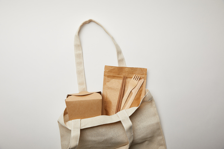 top view of cotton bag with noodle box, chopsticks and disposable forks with knives on white surface