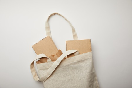 flat lay with cotton bag with food boxes and chopsticks on white surface
