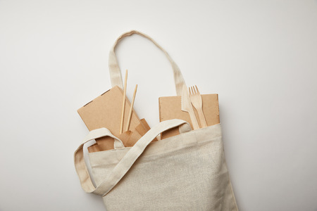 top view of cotton bag with food boxes, chopsticks and disposable forks with knives on white surface Reklamní fotografie