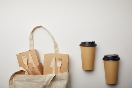 view from above of cotton bag with food boxes and two disposable coffee cups on white surface Reklamní fotografie