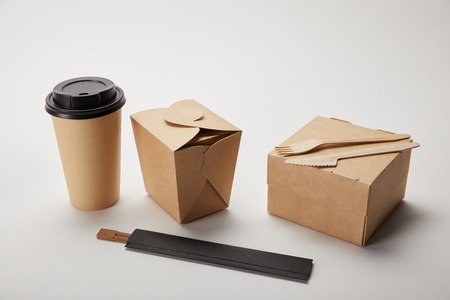 disposable fork with knife, paper coffee cup, food boxes and chopsticks on white