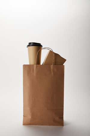 close up view of food delivery paper bag with disposable coffee cup and wok box on white Stockfoto