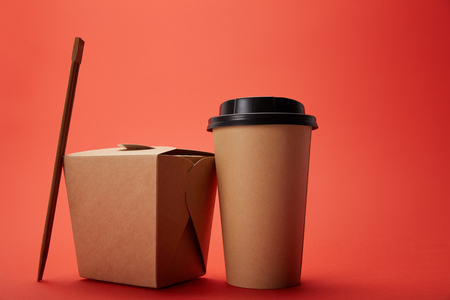 close up view of noodle box, paper cup of coffee with chopsticks on red, minimalistic concept