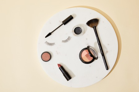top view of various cosmetics lying on round plate