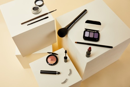 high angle view of various makeup accessories on beige cubes 스톡 콘텐츠