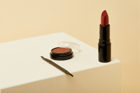 close-up shot of lipstick standing on beige surface with can of blush and brush 스톡 콘텐츠