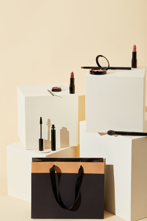 various makeup supplies lying on beige cubes with paper bag Stock Photo