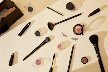 top view of different cosmetics and false eyelashes lying on beige tabletop