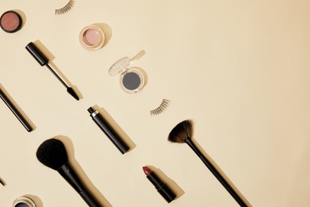 flat lay with composition of different cosmetics lying on beige tabletop