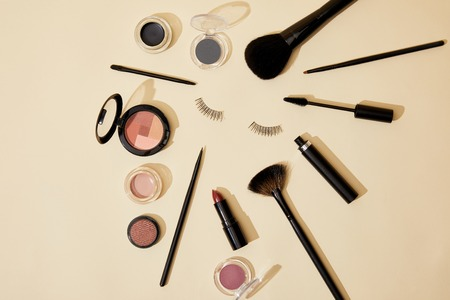 top view of different cosmetics lying on beige surface around false eyelashes 스톡 콘텐츠