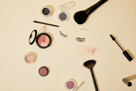 top view of various cosmetics lying on beige surface 스톡 콘텐츠