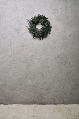 green fir wreath for Christmas decoration hanging on grey wall in room