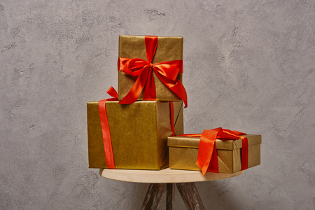 golden Christmas gift boxes with red ribbons on chair near grey wall in room