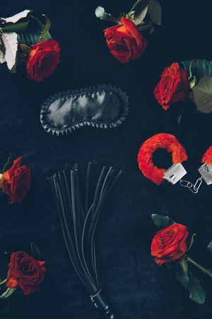 top view of black mask, leather whip and red fluffy handcuffs with roses Stock Photo - 110463681