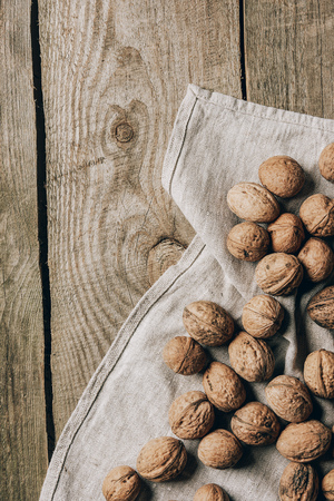 top view of whole tasty healthy walnuts on cloth on wooden table
