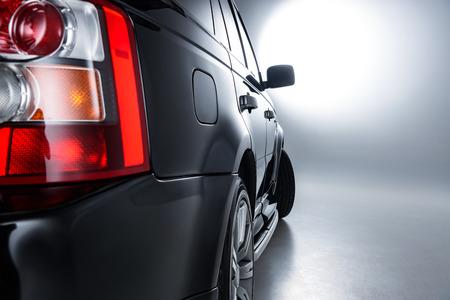 Close up view of rear headlight rear of luxury black car on grey backdrop Reklamní fotografie