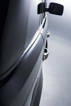 close up view of black luxury car on grey background