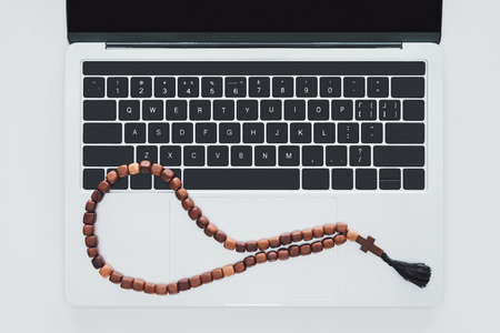 top view of beads lying on laptop on white surface Stock Photo