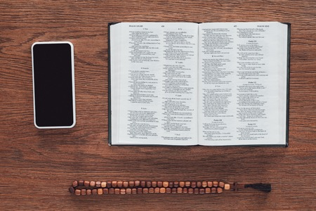 top view of opened holy bible with beads and smartphone on wooden table Stock Photo