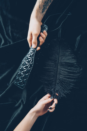 cropped shot of couple holding black feather and leather spanking paddle