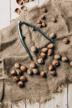 top view of tasty hazelnuts and nutcracker on sackcloth on wooden table