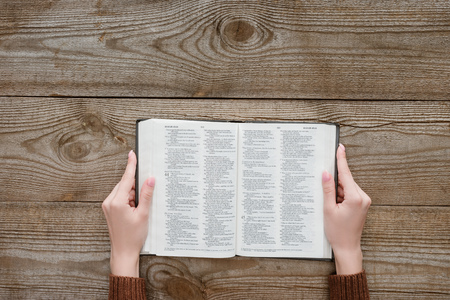 cropped shot of woman holding opened holy bible on wooden surface