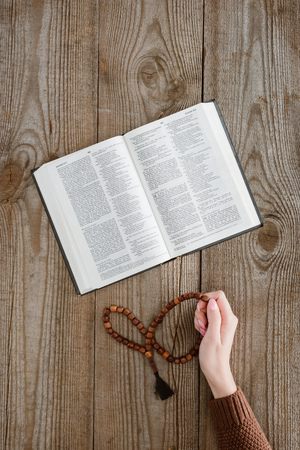 cropped shot of woman with holy bible holding beads on wooden table Stock Photo