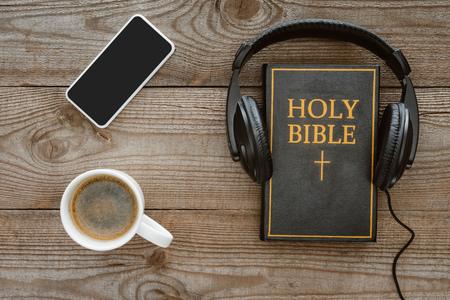 Draufsicht der Bibel mit Kopfhörern, Smartphone und Kaffee auf Holztischplatte Standard-Bild