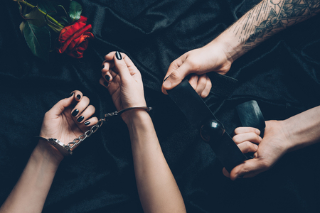 cropped shot of couple with handcuffs and gag above black fabric with rose flower