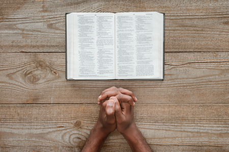 cropped shot of african american man praying with holy bible on rustic wooden table Imagens