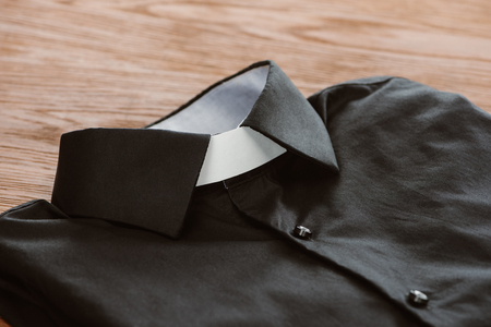 close-up shot of clerical shirt with white collar on wooden surface