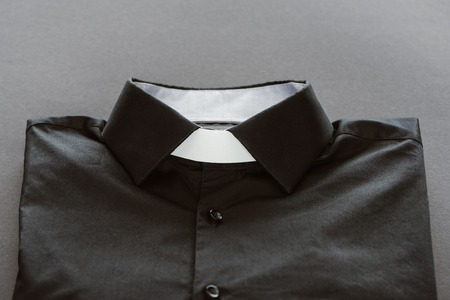 close-up shot of clerical shirt with white collar on grey surface Zdjęcie Seryjne - 110464236