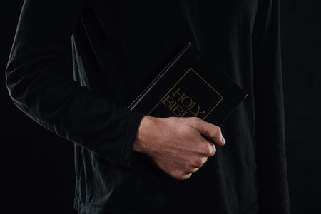 cropped shot of priest holding holy bible isolated on black Stockfoto