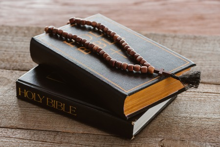close-up shot of stacked bible books with beads on wooden surface Stock Photo