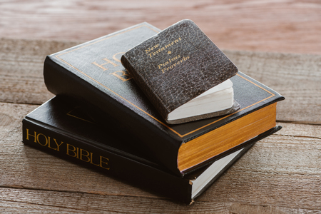 close-up shot of stacked holy bibles with new testament book on wooden surface