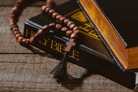 close-up shot of holy bibles with beads on wooden table Stock Photo