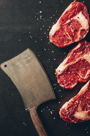 top view of raw meat steaks and cleaver on surface in kitchen Stock Photo