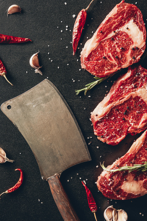 top view of raw meat steaks, spices and cleaver on surface in kitchen Stock Photo