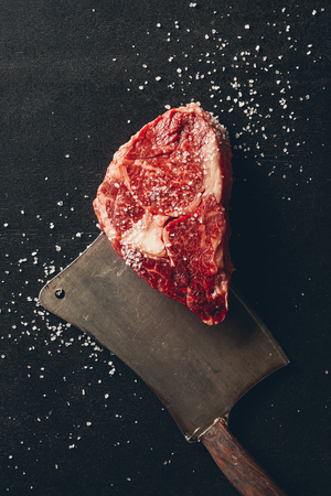 top view of raw meat steak, salt and cleaver on tabletop in kitchen Stock Photo